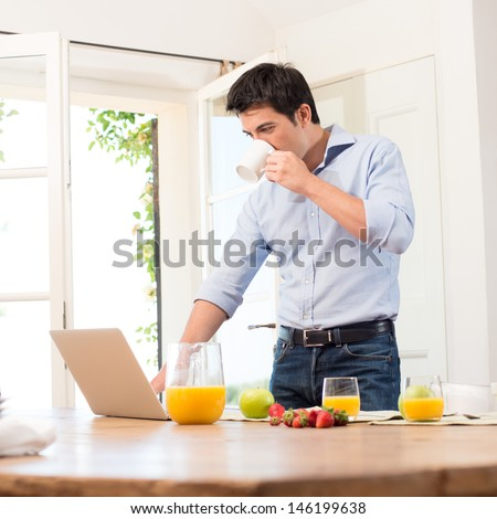 Portrait Of Young Man Using Laptop While Having Breakfast - stock photo