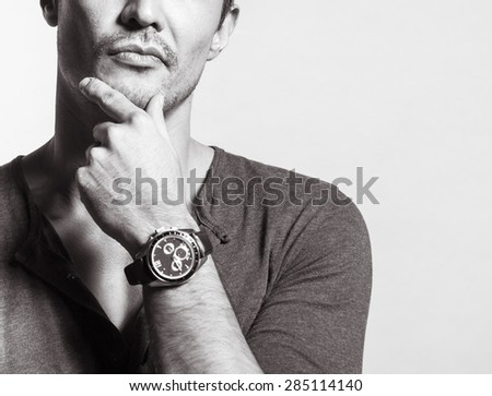 Portrait of young man wearing a watch in deep thought - stock photo