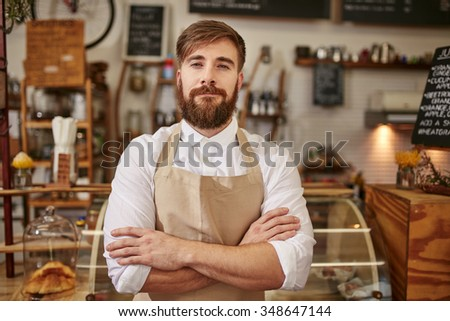 Portrait of young man wearing apron standing with his arms crossed in a coffee shop. Caucasian man with beard standing in a cafe looking at camera. - stock photo