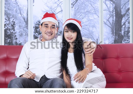 Portrait of young man wearing christmas hat and embrace his girlfriend on sofa at home