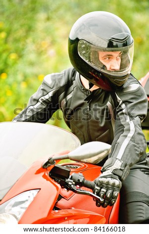 Portrait of young man wearing helmet, leather costume, driving red motorbike.