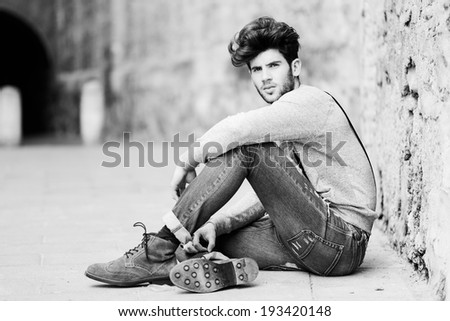 Portrait of young man wearing suspenders and blue jeans in urban background with modern haircut, sitting on the floor - stock photo