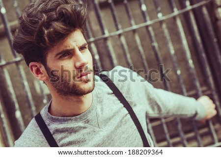 Portrait of young man wearing suspenders in urban background - stock photo