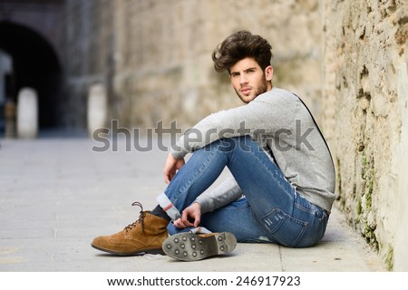 Portrait of young man wearing suspenders sitting on the floor in urban background