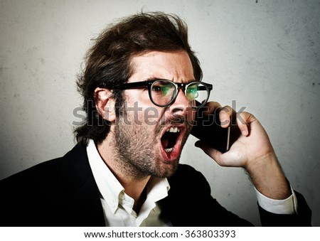 Portrait of young man wearing trendy suit and screaming on his smartphone. Horizontal