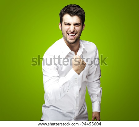 portrait of young man winner gesture against a green background