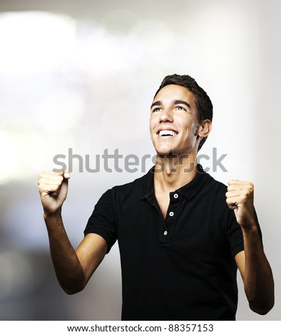 portrait of young man winning against a abstract background - stock photo