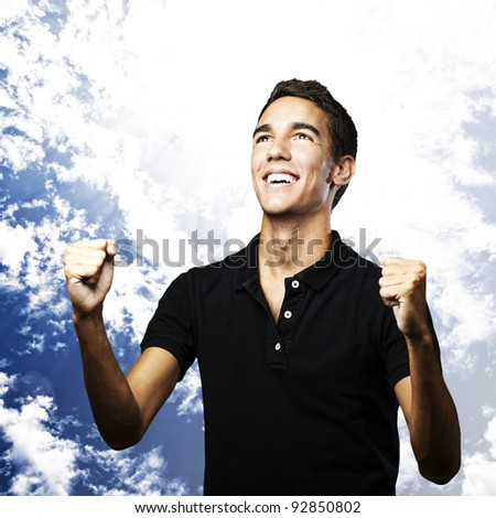 portrait of young man winning against a cloudy sky background - stock photo