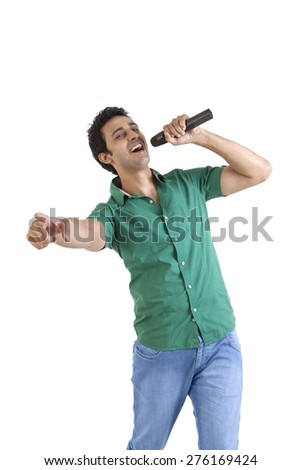 Portrait of young man with a microphone singing - stock photo