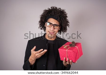 Portrait of young man with afro holding a Christmas gift - stock photo