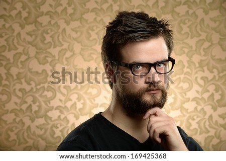 Portrait of young man with beard and glasses over retro background