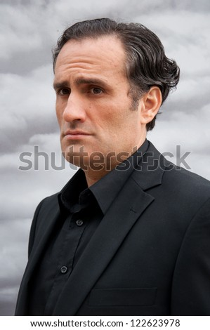 portrait of young man with black curly hair,in elegant suit,gray clouds background - stock photo