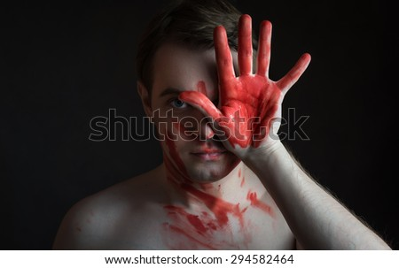 Portrait of young man with blood on his face and palm on dark background. - stock photo