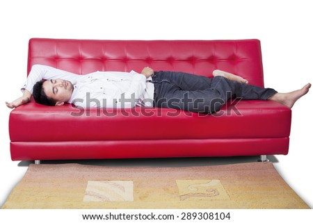 Portrait of young man with casual clothes sleeping on the red sofa, isolated on white - stock photo