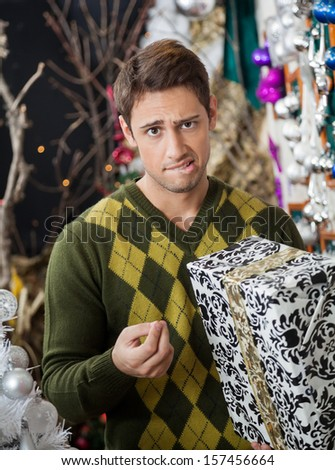 Portrait of young man with Christmas gift biting lips in store - stock photo