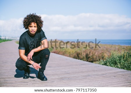 portrait of young man with dark skin, mixed race, big African hair, sitting outdoor on sea shore