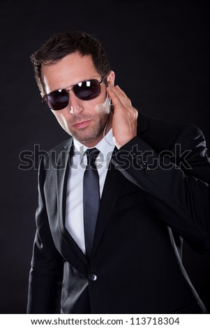Portrait Of Young Man With Earphone On Black Background - stock photo