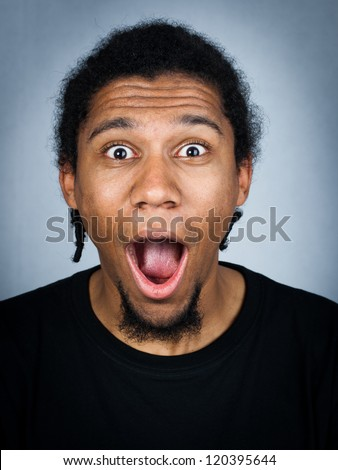 Portrait of young man with emotional facial expression - shocked man - stock photo