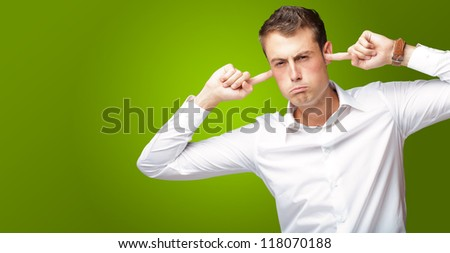Portrait Of Young Man With Finger In His Ear On Green Background - stock photo
