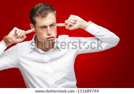 Portrait Of Young Man With Finger In His Ear On Red Background - stock photo