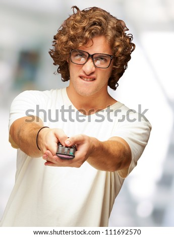 Portrait Of Young Man With Glasses Changing Channel With Tv Control, Indoor - stock photo