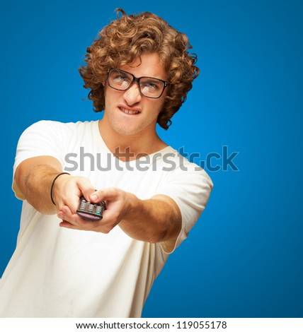 Portrait Of Young Man With Glasses Changing Channel With Tv Control On Blue Background - stock photo