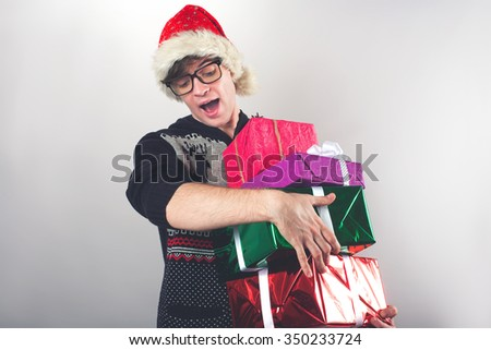 Portrait of young man with glasses holding a Christmas gifts - stock photo