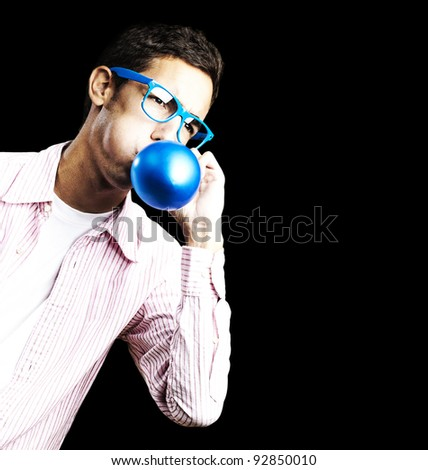 portrait of young man with glasses inflating a blue balloon against a white background
