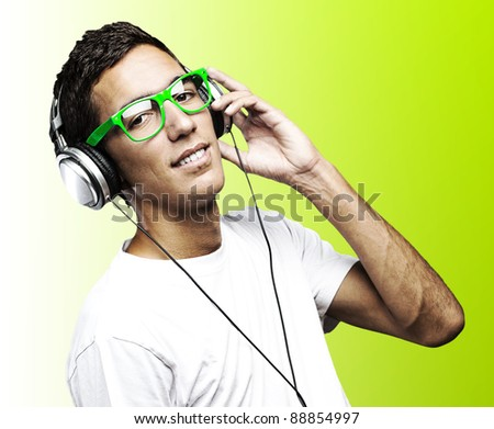 portrait of young man with green glasses listening to music on a green background - stock photo