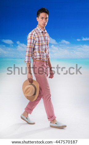 portrait of young man with hat  walking at beach background