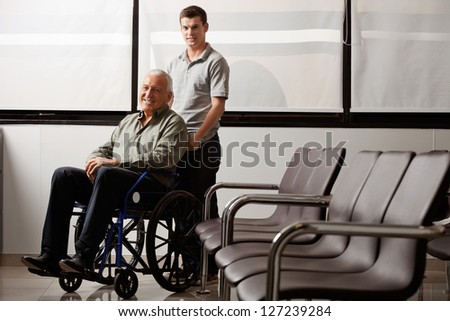 Portrait of young man with his grandfather on wheelchair in hospital lobby - stock photo