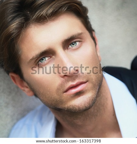 portrait of young man with impressive green eyes - stock photo
