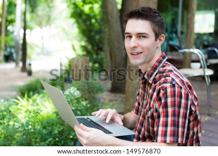Portrait of young man with laptop outdoor - stock photo