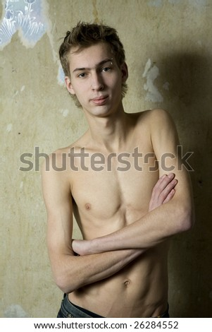 portrait of young man with pirsing in eyebrow standing at the wall