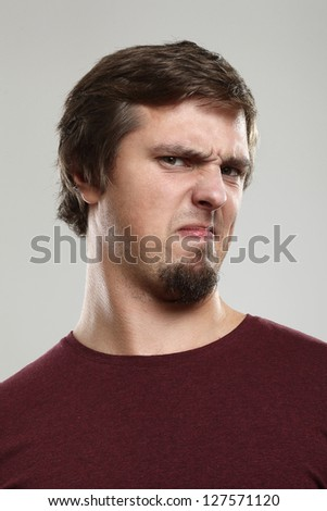 Portrait of young man with repulsion expression  isolated over background - stock photo