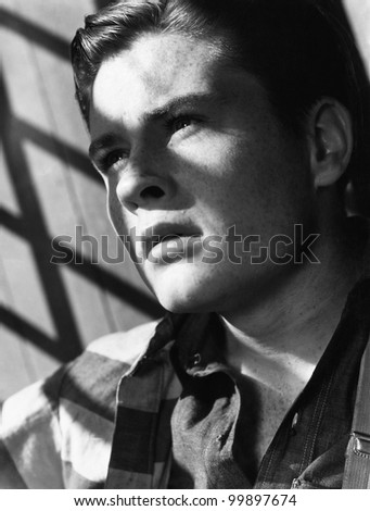 Portrait of young man with shadow of bars - stock photo
