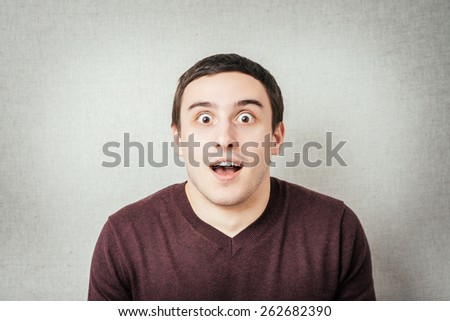Portrait of young man with shocked facial expression, - stock photo