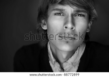 Portrait of young man with smart and wise look. Looking at camera. Black and white photo