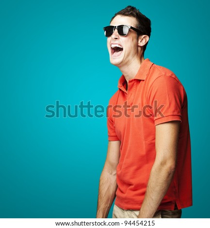 portrait of young man with sunglasses laughing over blue background - stock photo