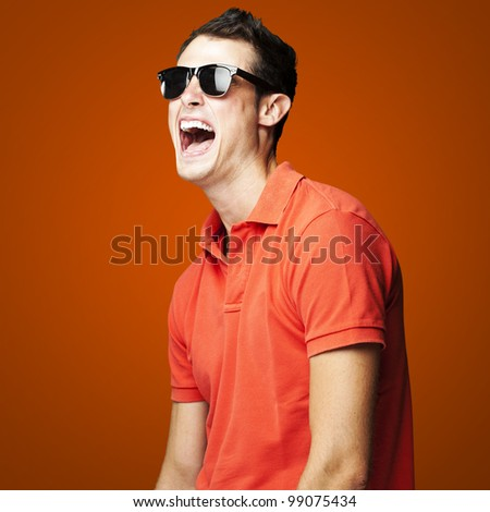 portrait of young man with sunglasses laughing over red background - stock photo