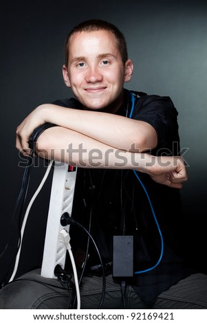 Portrait of young man with the wires on a dark background (studio version)