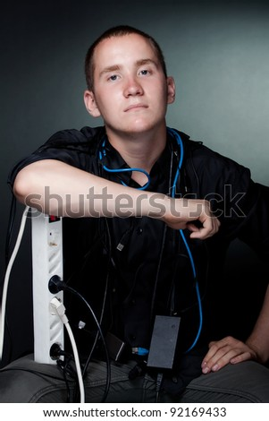 Portrait of young man with the wires on a dark background (studio version) - stock photo