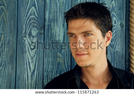 Portrait of young man with very handsome face in black shirt against natural background