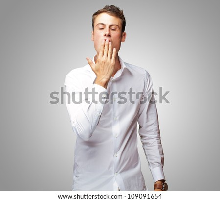 Portrait Of Young Man Yawning Isolated On Gray Background - stock photo
