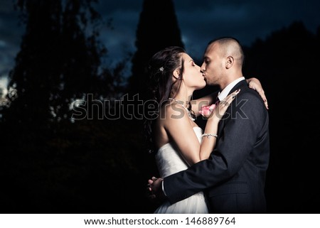 Portrait Of Young Married Couple Kissing Outdoors - stock photo