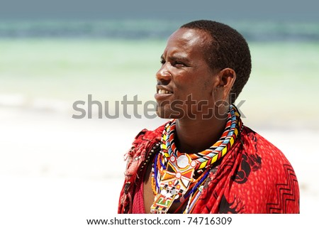 Portrait of young Masai man posing on beach; portrait with narrow focus - stock photo