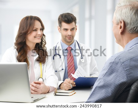 Portrait of young medical team sitting at desk and discussing with elderly patient at private clinic.