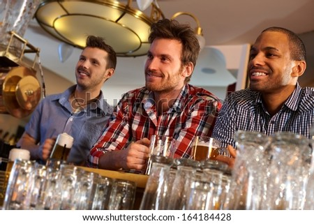 Portrait of young men drinking beer at bar counter, smiling. - stock photo