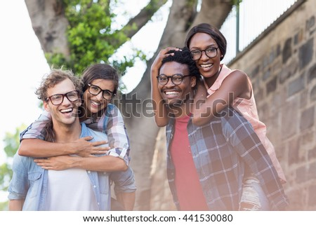 Portrait of young men giving piggyback to women - stock photo