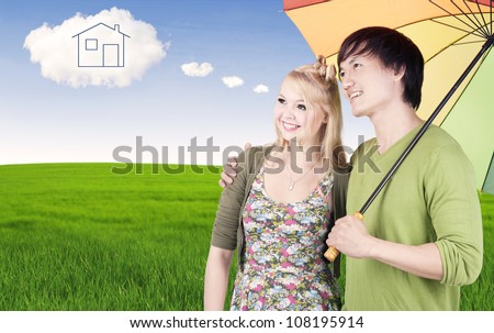 Portrait of young mixed couple under multicolored umbrella looking at dream house on the cloud - stock photo